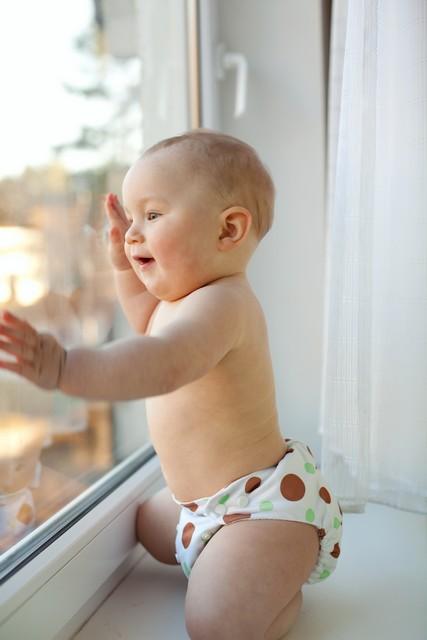 happy baby boy looks through the window
